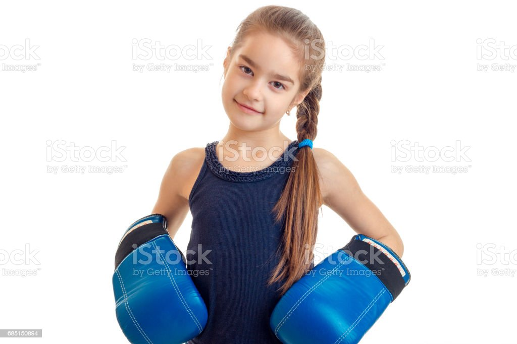 cute little baby-girl standing in front of the camera in big boxing gloves is isolated on a white background royalty-free stock photo