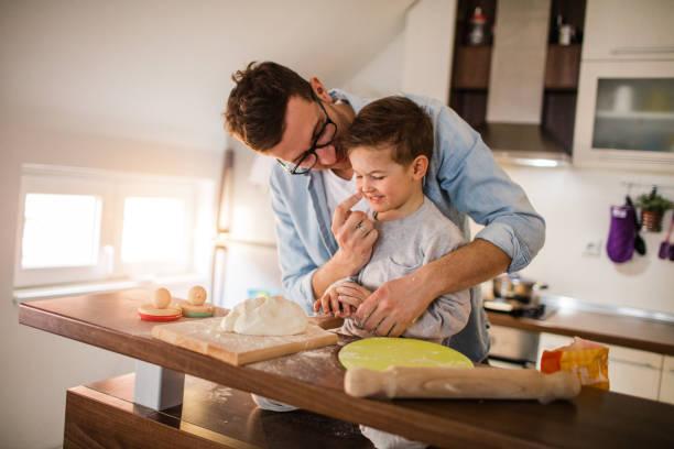 cute little baker and his father - baking bread at home imagens e fotografias de stock