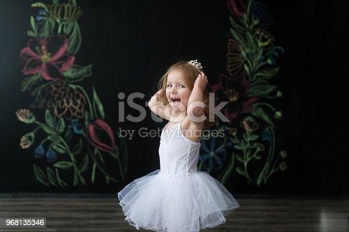 istock Cute little ballerina in white ballet costume is dancing in the room. Kid in dance class. 968135346