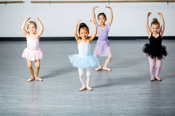 Cute Little Ballerinas Practicing in Dance Studio A cute diverse group of ballerinas practicing at their dance studio. dance studio stock pictures, royalty-free photos & images