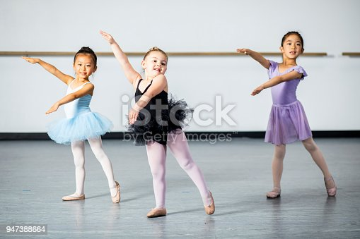 A cute diverse group of ballerinas practicing at their dance studio.