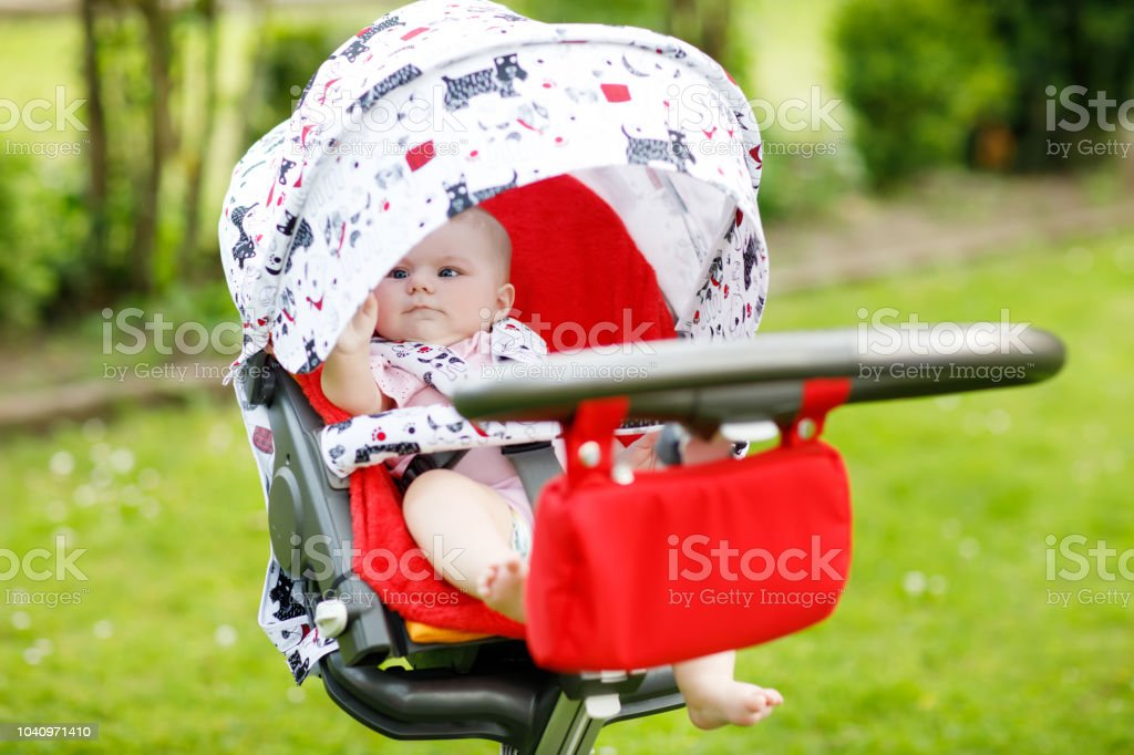 Cute little beautiful baby girl of 6 months sitting in the pram or stroller and waiting for mom royalty-free stock photo