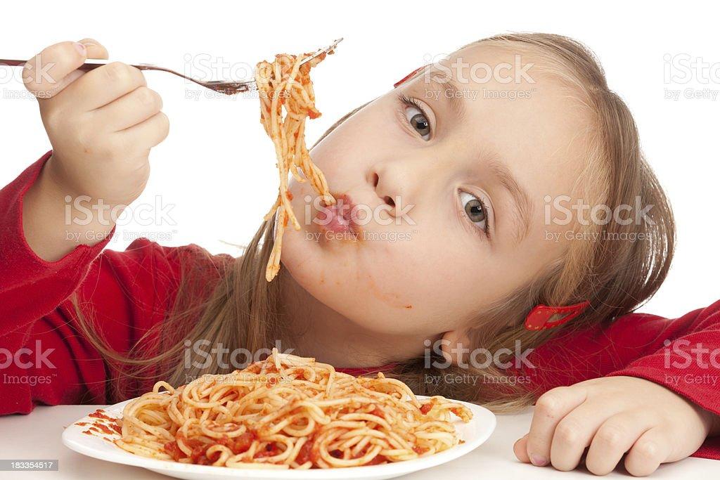 Cute little blond girl eating spaghetti royalty-free stock photo
