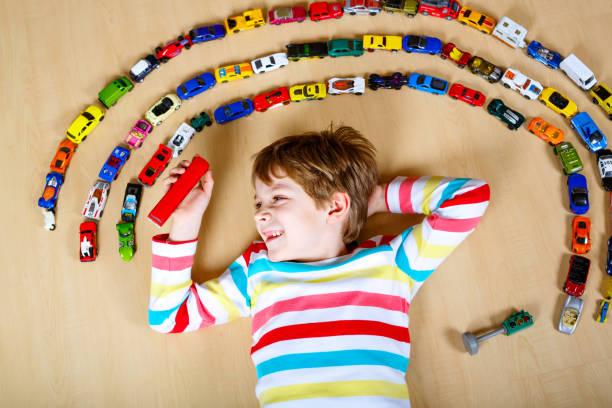 niedliche kleine blonde kind junge spielt mit viel spielzeug-autos - spielesammlung stock-fotos und bilder