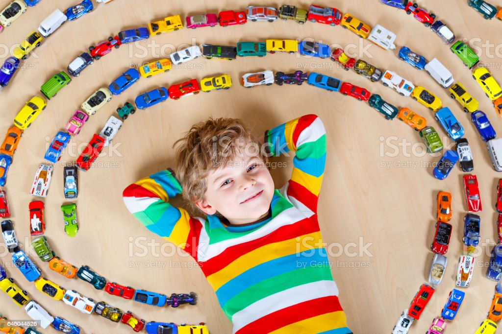 Cute little blond kid boy playing with lots toy cars – Foto