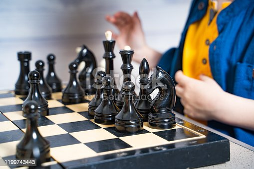 Young child playing chess on large board. Logic developing board games concept.
