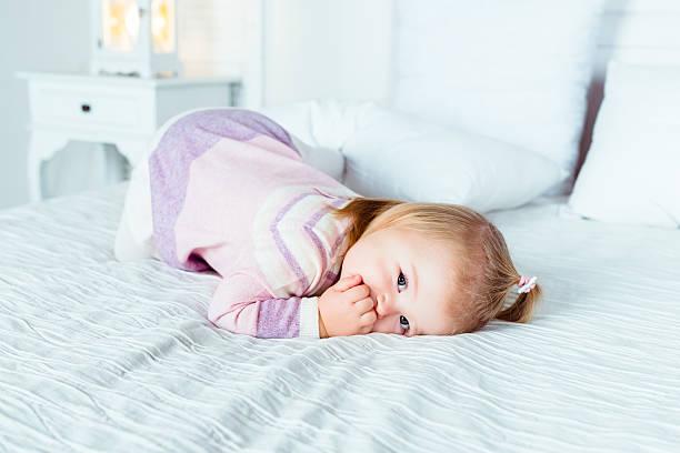 Ein niedliches kleines blonde Mädchen auf Händen und Knien auf dem Bett – Foto