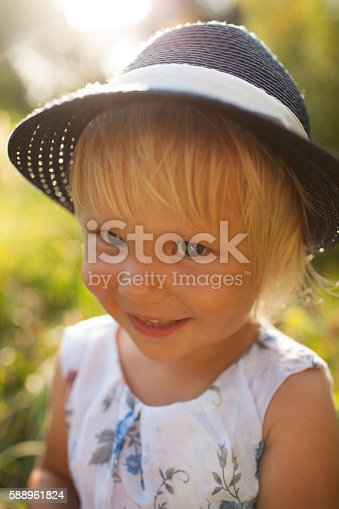 istock Cute little blonde smiling girl in a blue hat 588961824