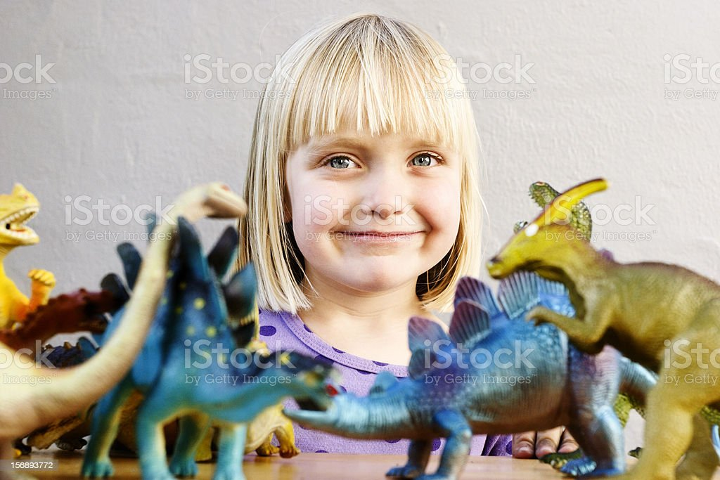 Cute little blonde with toy dinosaurs smiles stock photo