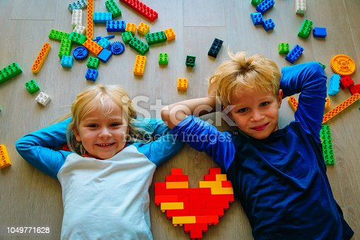 istock cute little boy and girl love playing with plastic blocks 1049771628