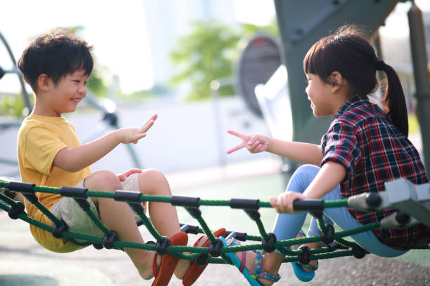 cute little boy and girl playing a rock-paper-scissors game - two students together asian foto e immagini stock