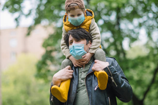 Cute little boy and his father smiling behind protective mask outdoors