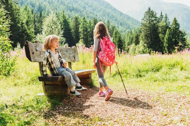 Netter kleiner Junge und seine Schwester mit Rucksack wandern in Bergen, auf einer Bank ausruhen – Foto