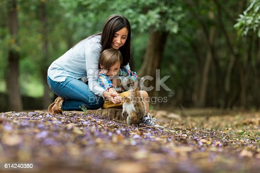 A cute latin little boy and his mother feeding a squirrel at the natural park in a horizontal full length shot outdoors.