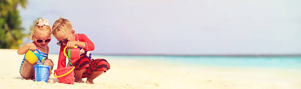 cute little boy and toddler girl play on beach stock photo