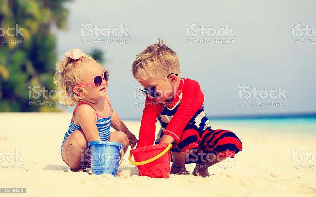 Süße kleine Junge und Mädchen spielen am Strand Lizenzfreies stock-foto
