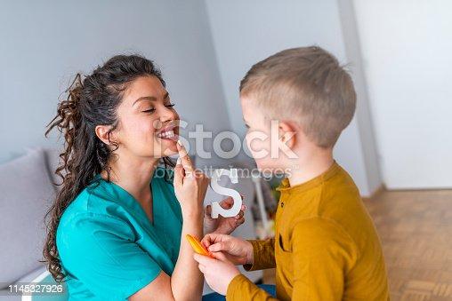 843899350istockphoto Cute little boy at speech therapist office 1145327926