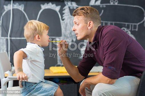 843899350istockphoto Cute little boy at speechtherapist session. 1170561984
