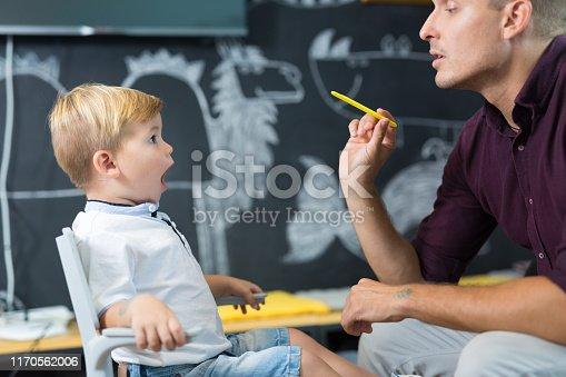 843899350istockphoto Cute little boy at speechtherapist session. 1170562006