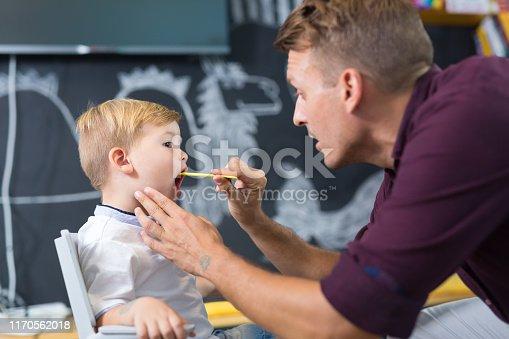 843899350istockphoto Cute little boy at speechtherapist session. 1170562018
