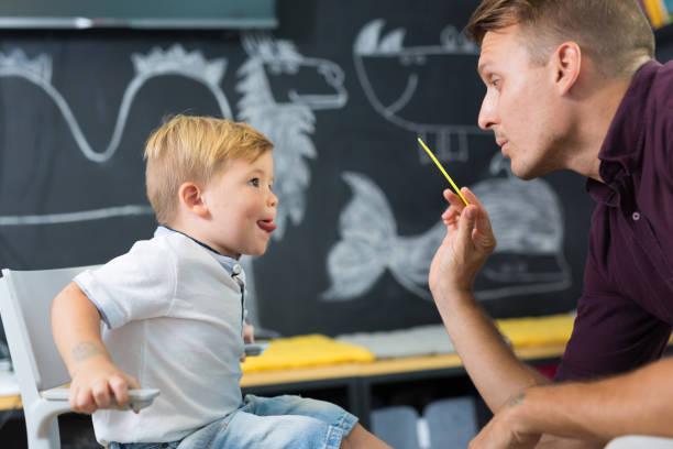 niedliche kleine junge speechtherapist tagung. - lautbildungsspiele stock-fotos und bilder