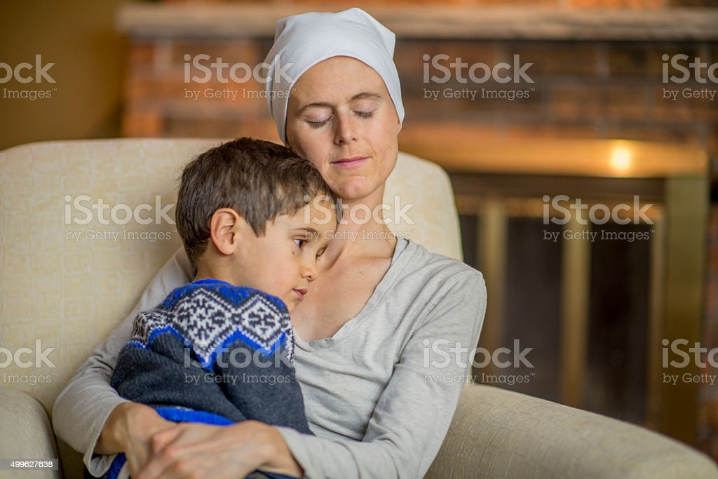 Cute Little Boy Being Held by His Sick Mother stock photo