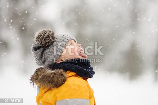 Cute little boy catching snowflakes with her tongue in beautiful winter park. Outdoors winter activities for kids.