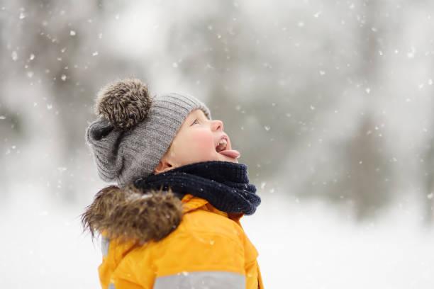 lindo niño cogiendo copos de nieve con su lengua en el hermoso parque de invierno - invierno fotografías e imágenes de stock