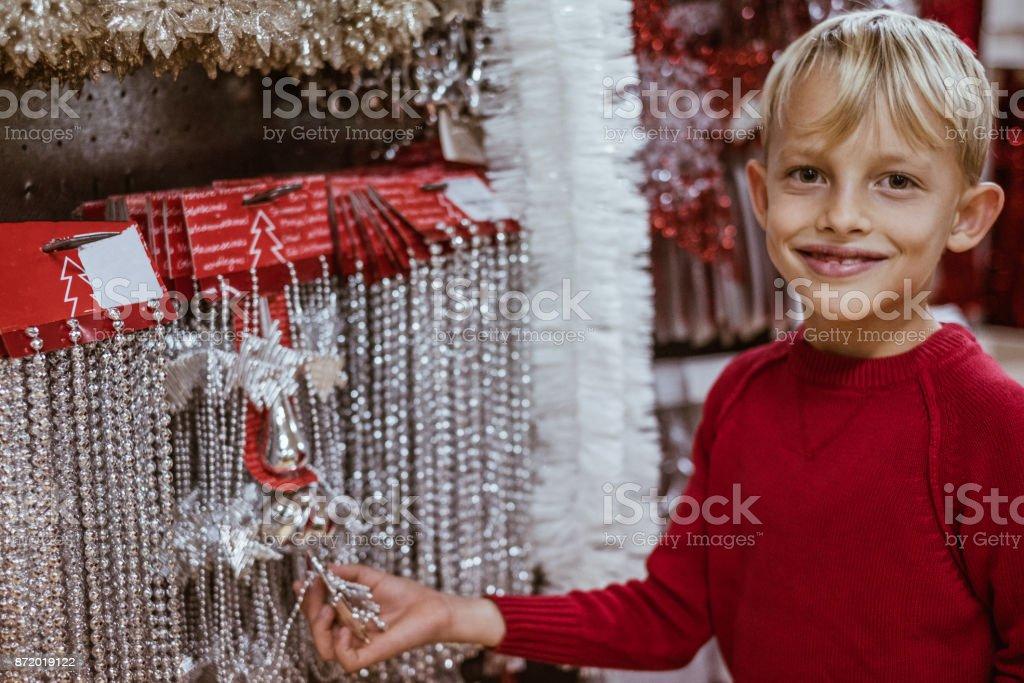 Cute little boy chosing christmas tree decoration in market store stock photo