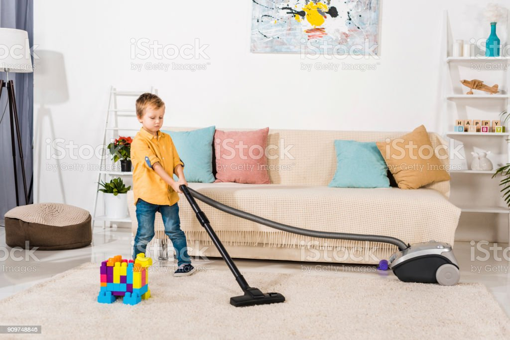 cute little boy cleaning carpet with vacuum cleaner stock photo