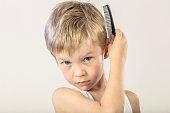A cute little boy combing his hair