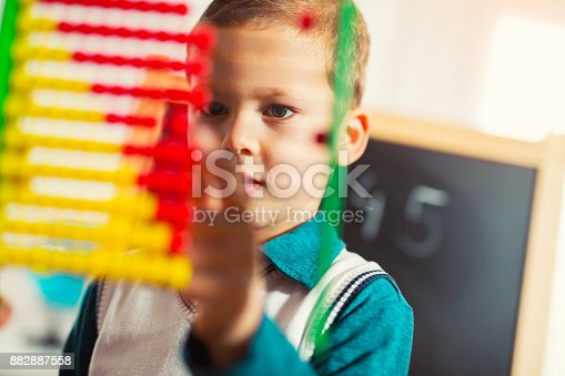 157230867istockphoto Cute little boy counting with abacus 882887558