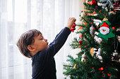 Cute little boy decorating christmas tree