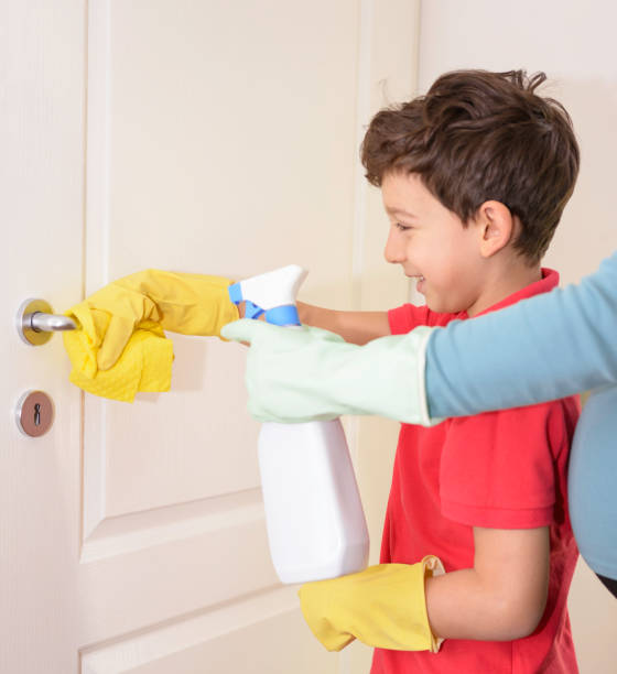 Cute little boy disinfecting doorknob. Helping his pregnant mom. stock photo