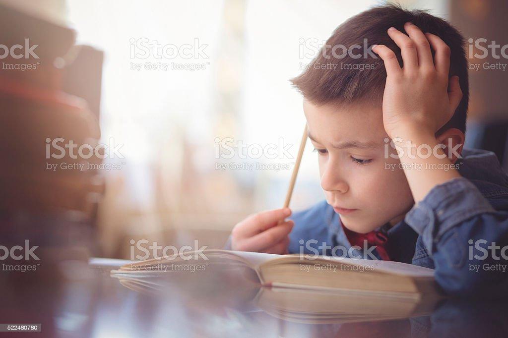 Cute little boy doing his homework stock photo