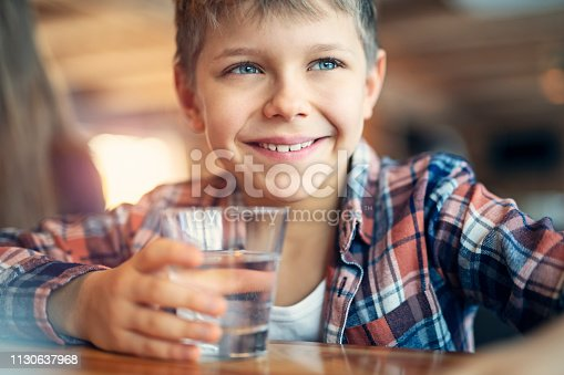 Portrait of a cute little boy drinking a glass of water. The boy is 9 years old. Nikon D850