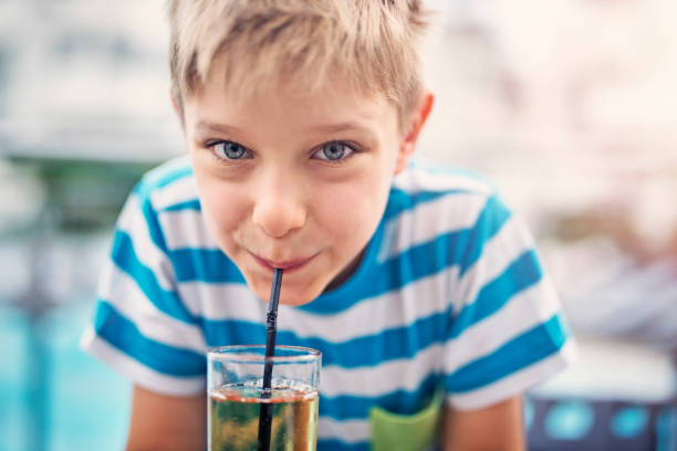 Cute little boy drinking apple juice at hotel restaurant stock photo