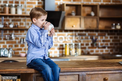 istock Cute little boy drinking milk 1078231442