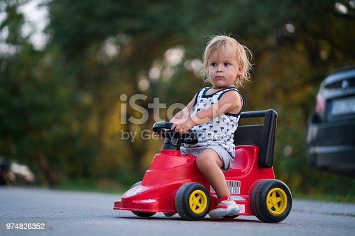Small boy enjoying while riding toy vehicle outdoors.