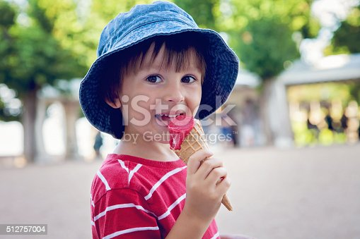 istock Cute little boy, eating big ice cream in the park 512757004