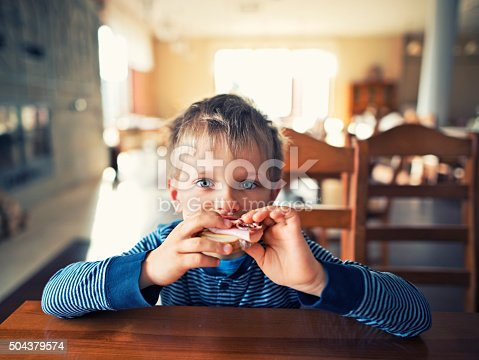 Cute little boy eating breakfast sandwich with ham and cheese in restaurant or home. The boy aged 5 and looking at the camera while biting the sandwich.