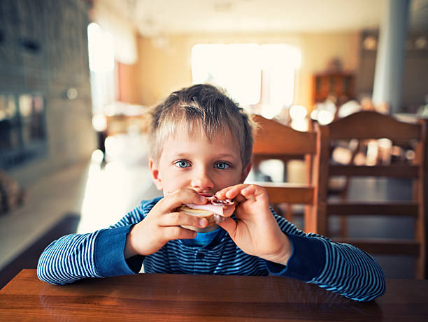 cute little boy eating breakfast - cheese sandwich bildbanksfoton och bilder