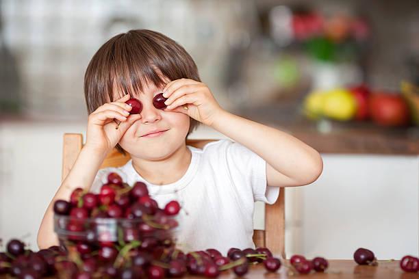 Linda niño pequeño, comida cherries en su casa en la cocina - foto de stock