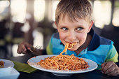 Happy little boy aged 7 is eating spaghetti lunch. The boy is smiling and looking sideways. \nNikon D810