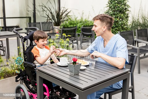 istock Cute little boy excited on a wheelchair and nurse giving him food both smiling 1055956124