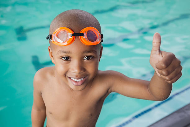 cute little boy giving thumbs up at the pool - swimmingpool kids stockfoto's en -beelden