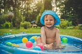 Happy child enjoying summer in swimming pool at back yard