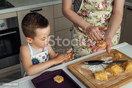 Cute little boy helps her mother prepare cookies. Family dessert