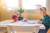 Cute little boy in bunny ears sitting at the table, full of Easter tiny things, holding a paintbrush in one hand and an colorful Easter egg in another
