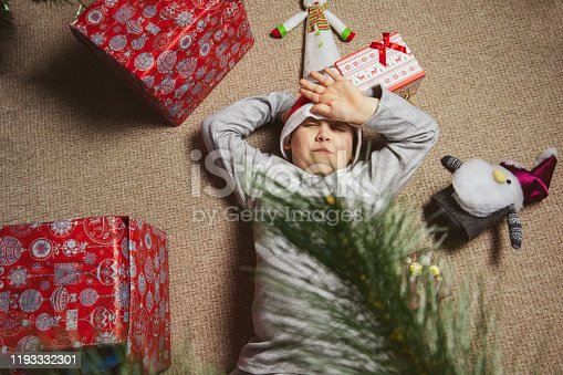 Bad Christmas. Little baby elf with present box crying near Xmas tree, waiting for gifts